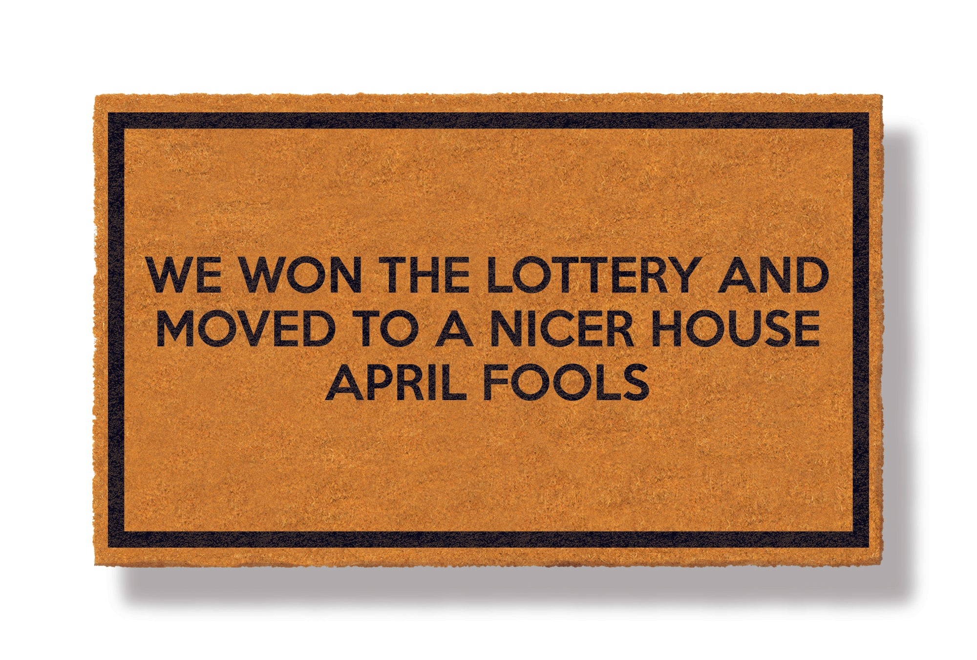 This coir welcome mat is a funny doormat on a white background with a drop shadow. The brown doormat has a black border and has black centered text that reads We Won The Lottery and Moved to a Nicer House APRIL FOOLS.