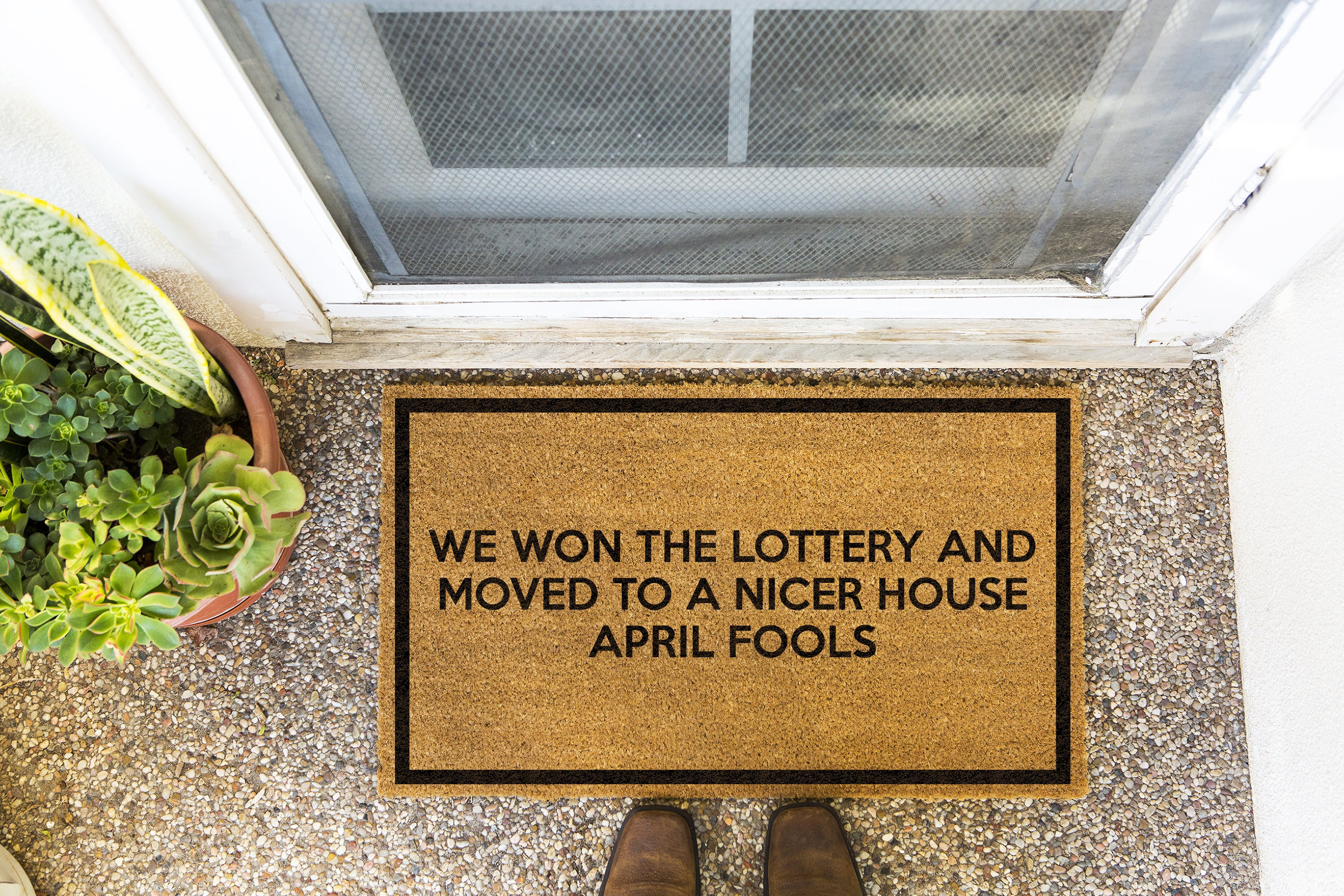 Brown doormat on a nice looking porch with shoes at the base of the mat.  The brown doormat has a black border and has black centered text that reads We Won The Lottery and Moved to a Nicer House APRIL FOOLS