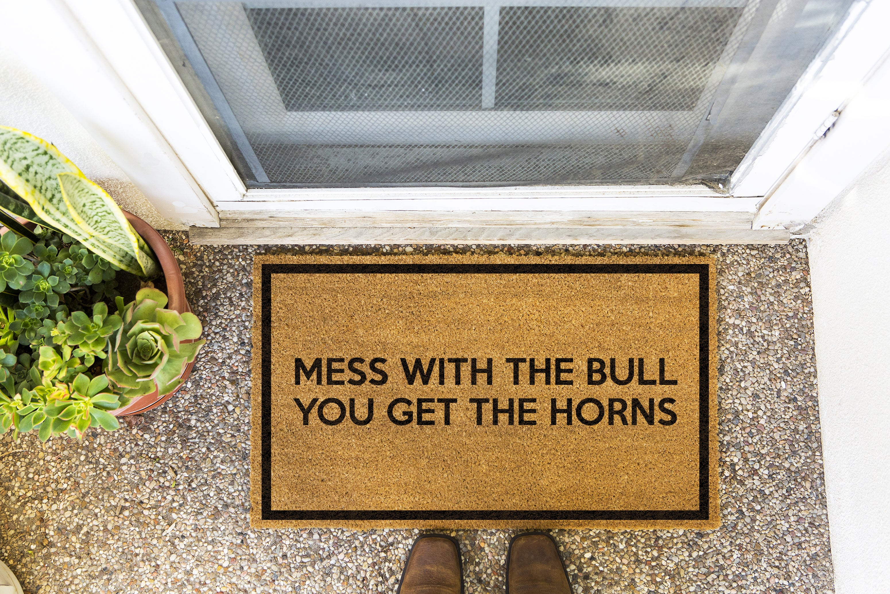 Brown doormat on a nice looking porch with shoes at the base of the mat.  The brown doormat has a black border and has black centered text that reads Mess With The Bull You Get The Horns