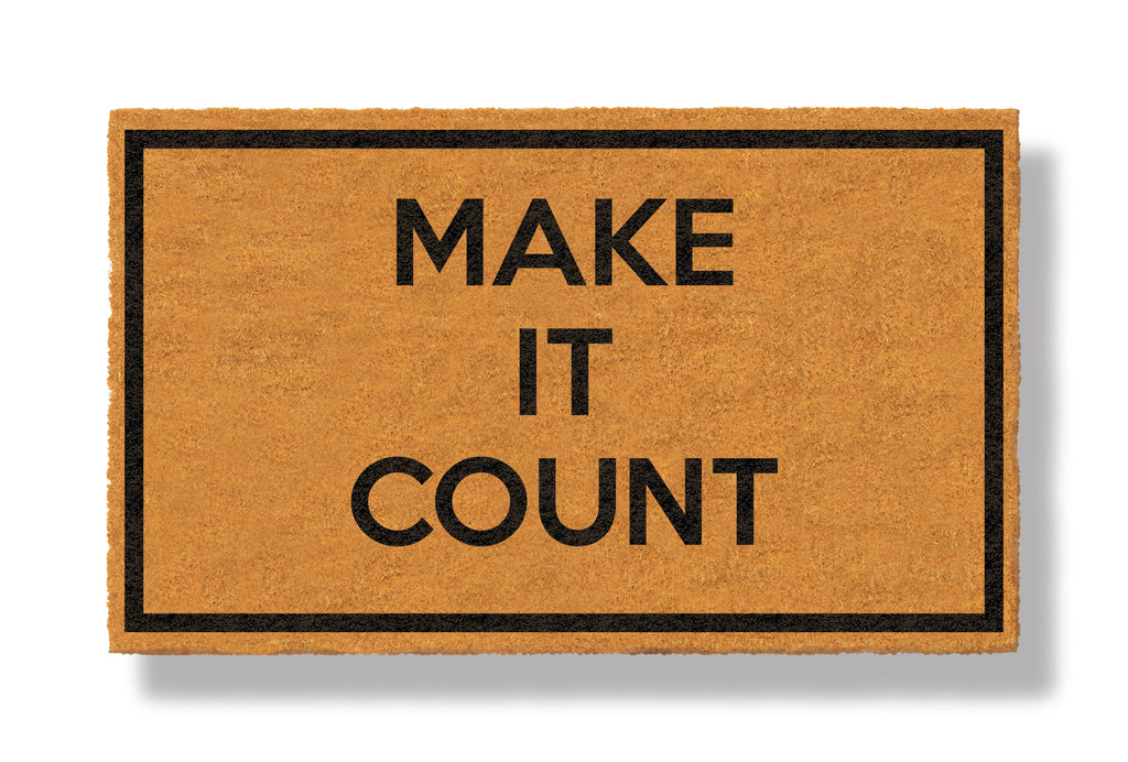 This coir welcome mat is a funny doormat on a white background with a drop shadow. The brown doormat has a black border and has black centered text that reads Make It Count.