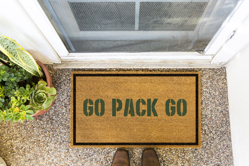 Brown doormat on a nice looking porch with shoes at the base of the mat.  The brown doormat has a black border and has black centered text that reads Go Pack Go