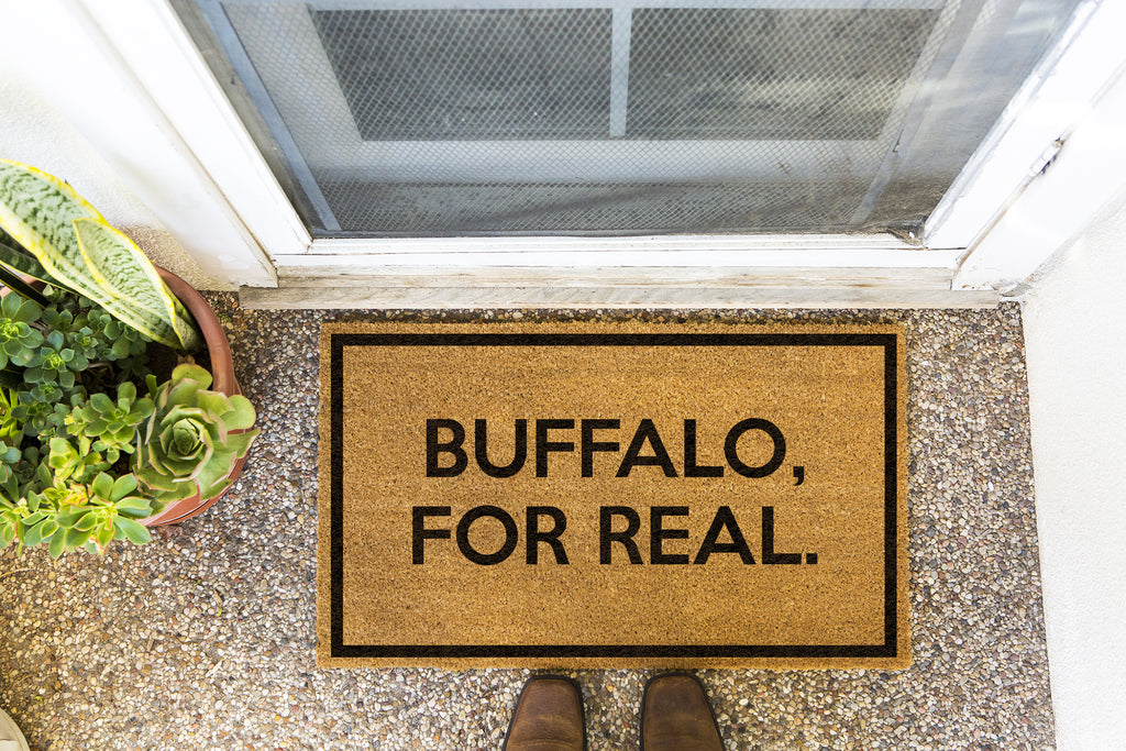 Brown doormat on a nice looking porch with shoes at the base of the mat.  The brown doormat has a black border and has black centered text that reads Buffalo, For Real.