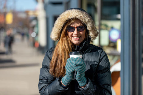woman wearing eykuver film on glasses in winter coat holding coffee with mittens