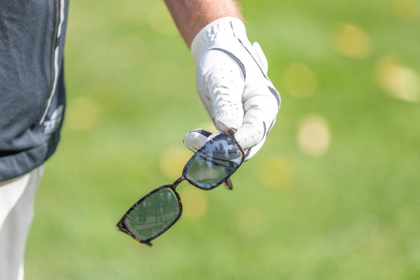golfer holding glasses with eykuvers on them in hand with golf glove on