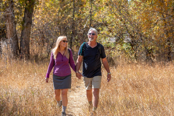 couple happily hiking with glasses on