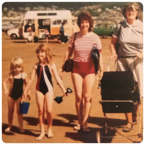 A photo from the 80s of two young girls, a mum and grandma on a beach with an ice cream van in the background
