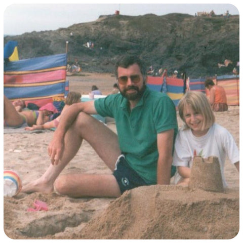 90s man and 90s child sitting on the beach