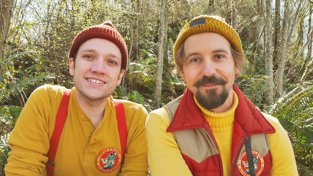 Authors Travis Bossard and Mick Szydlowski wearing adventure gear in a wooded area in the pacific northwest.