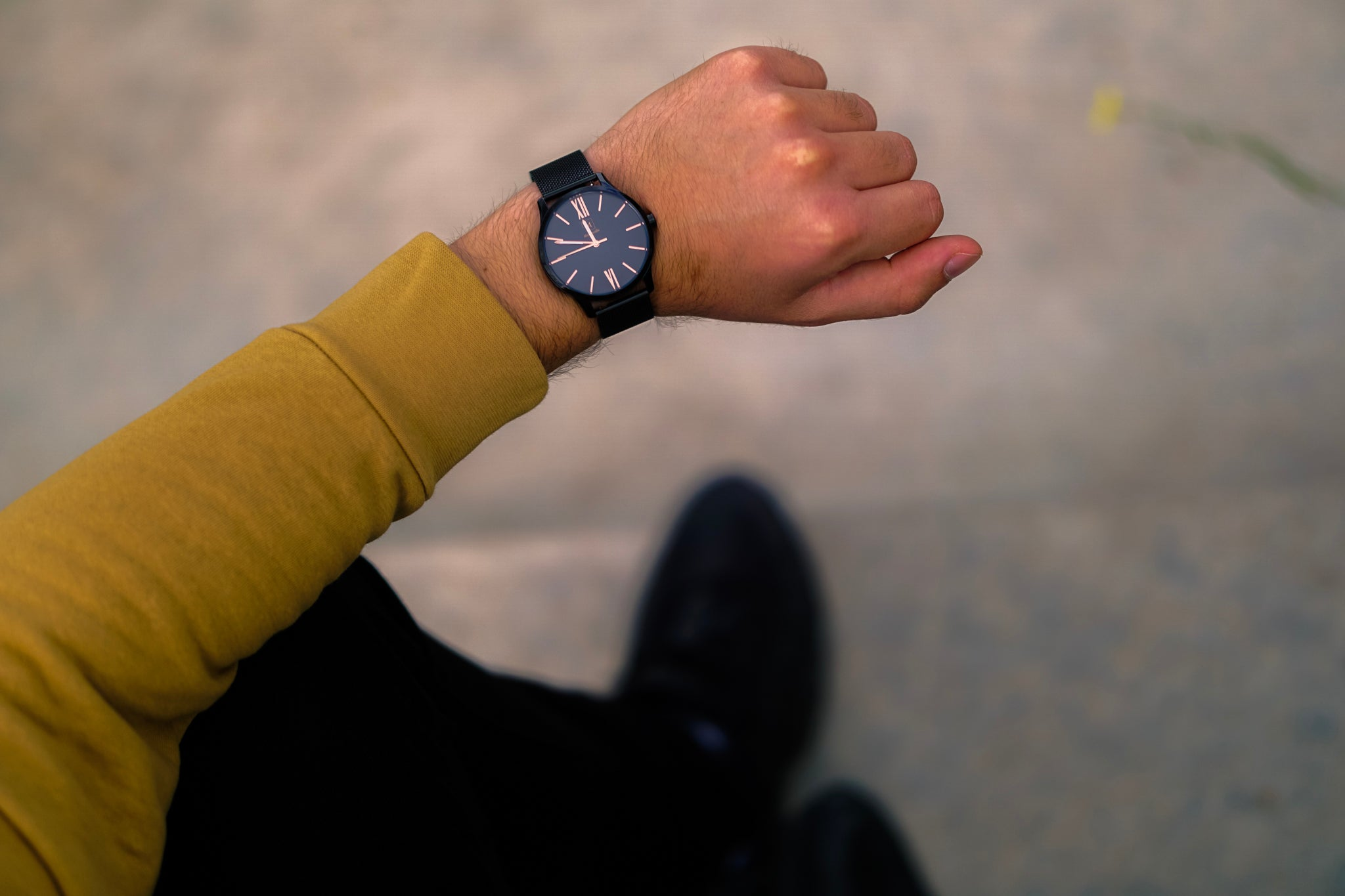 An image of a black watch from the brand Montreville. The watch is being worn by a man. On the picture you can only see the arm and hand of the man. The watch is called Houston and has rosé golden numerals. The design is elegant and stylish.
