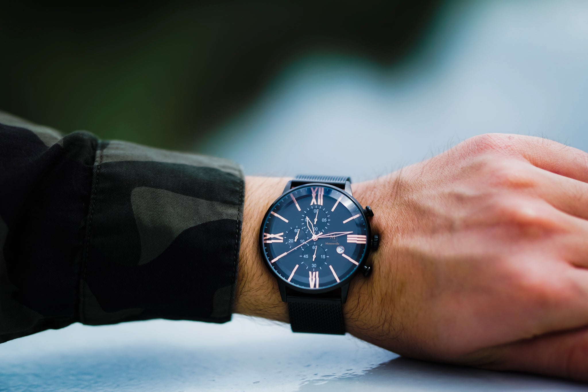 An image of a black watch from the brand Montreville. The watch is being worn by a man. On the picture you can only see the arm and hand of the man. The watch is called Baku and had rosée golden numerals, a chronometer and date. The timepiece has a unique design.