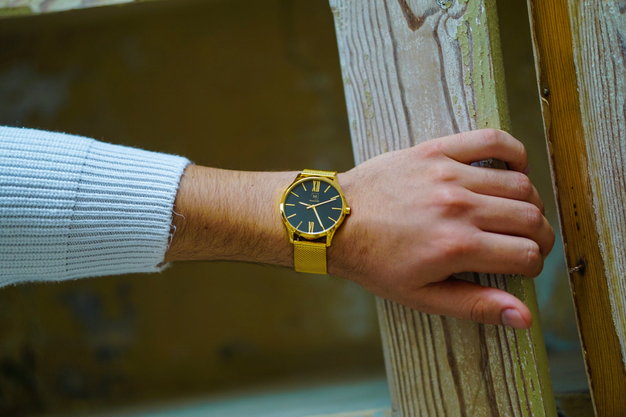An image of a gold watch from the brand Montreville. The watch is being worn by a man. On the picture you can only see the arm and hand of the man. The watch is called Luxor and has golden numerals. The design is elegant and stylish.