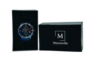 Blue watch called Jodhpur from the brand Montreville. This is an image of the watch inside a black, Montreville watch box. The timepiece has a unique design with large glass, roman numerals in rosé gold, a stopwatch and date. The model has a mesh strap in blue.