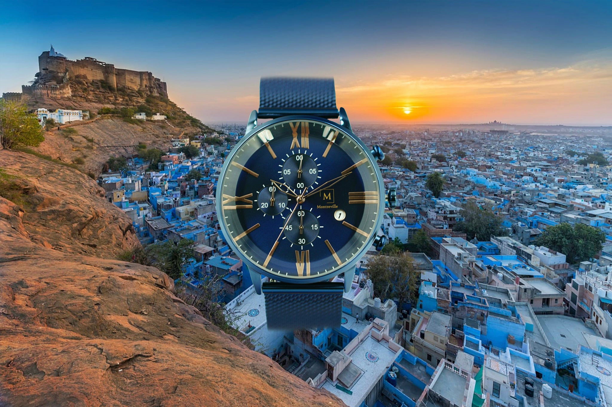 Blue watch called Jodhpur from the brand Montreville. This is an image of the watch with a picture of the city of Jodhpur in the background. The timepiece has a unique design with a large glass, roman numerals in rosé gold, a stopwatch and date. The Jodhpur timepiece has a mesh strap in blue.