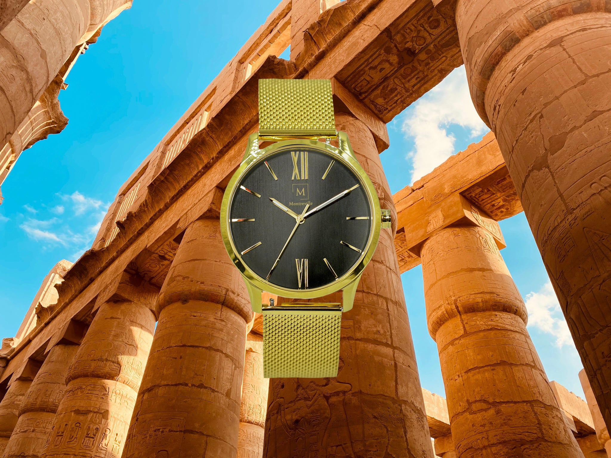 Gold watch called Luxor from the brand Montreville. This is an image of the watch with a picture of the city of Luxor in the background. The timepiece has an elegant design with roman numerals in gold and a mesh strap in gold.