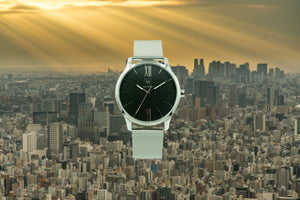 Silver watch called Tokyo from the brand Montreville. This is an image of the watch with a picture of the city of Tokyo in the background. The timepiece has an elegant design with roman numerals in silver and a mesh strap in silver.
