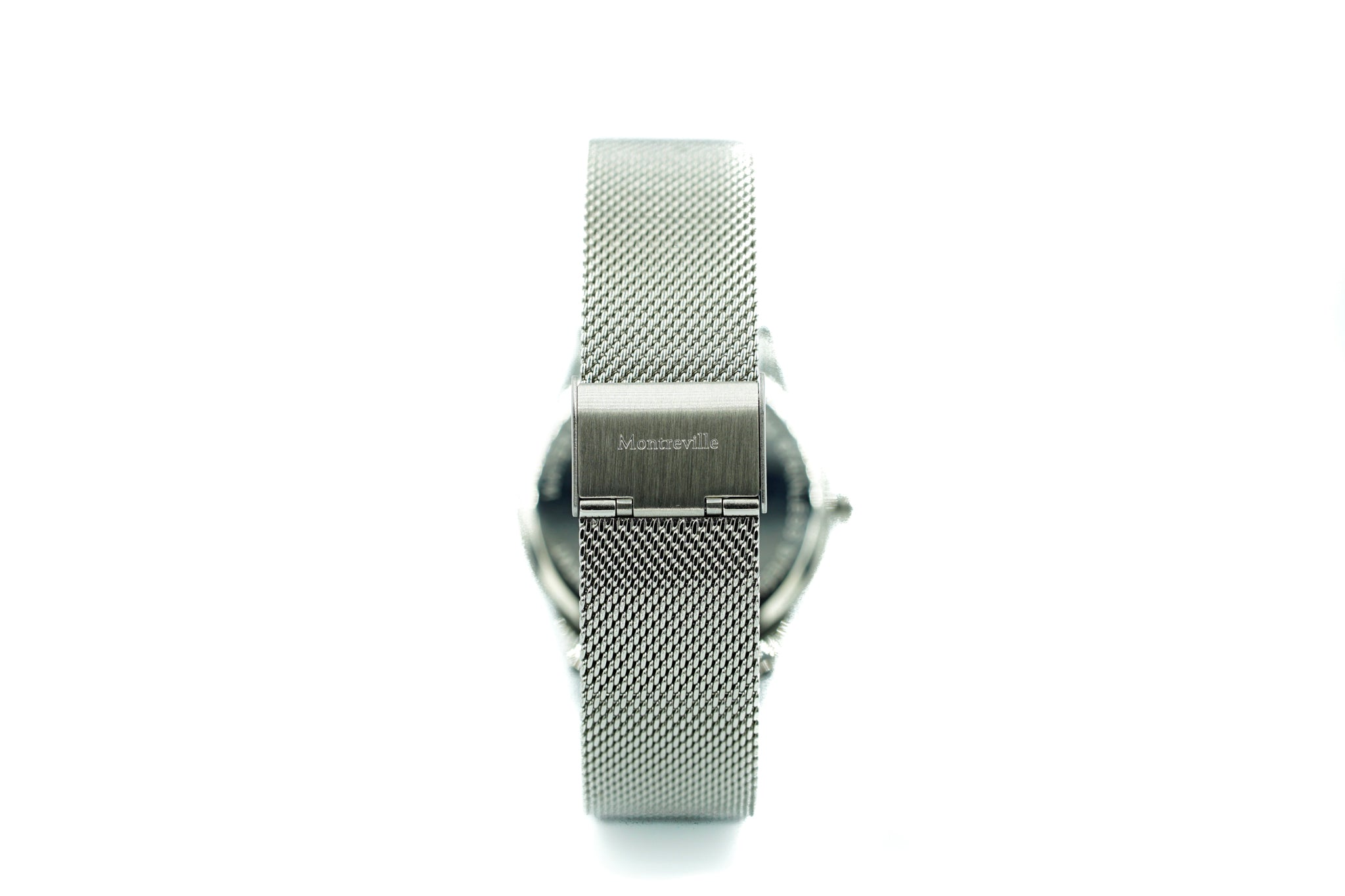 Silver watch called Tokyo from the brand Montreville, seen from the back. This is an image of the watch with a white background. The timepiece has an elegant design with a mesh strap in silver.