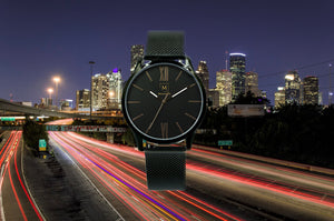 Black watch called Houston from the brand Montreville. This is an image of the watch with a picture of the city of Houston at night in the background. The timepiece has an elegant design with roman numerals in rosé gold and a mesh strap in black.