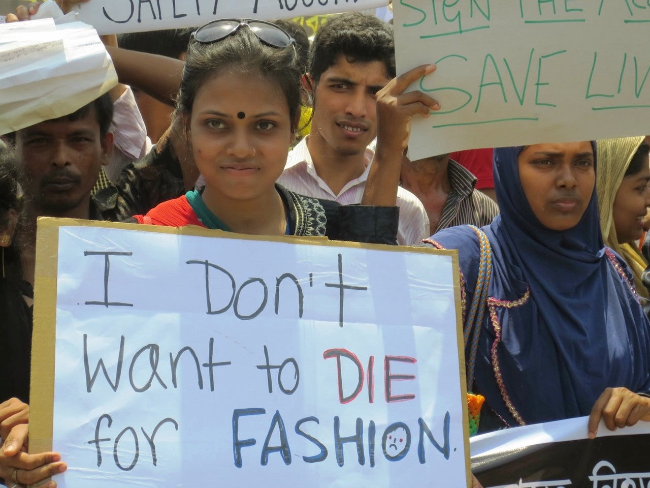 Garment worker holding fast fashion sign
