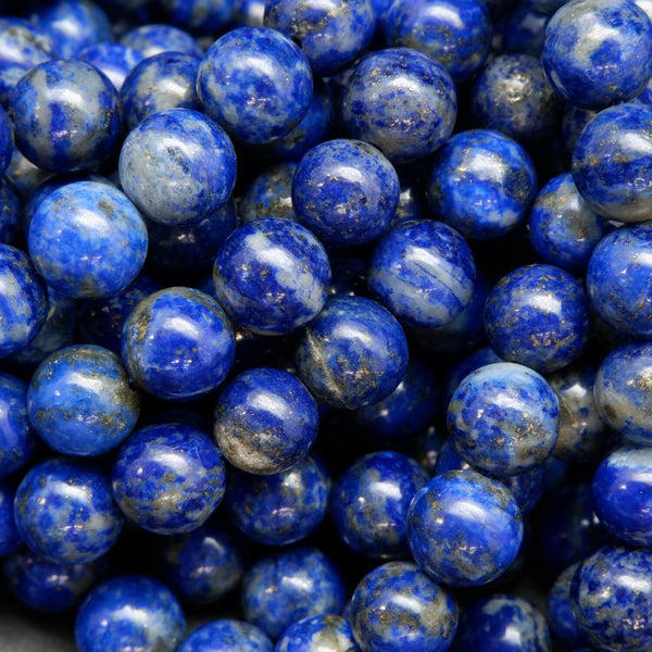 Blue round lapis lazuli beads with calcite and pyrite inclusions.