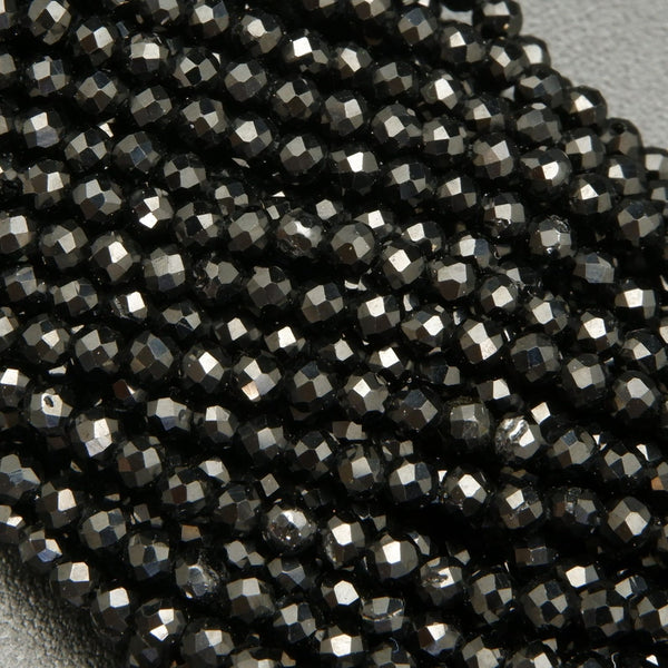 Faceted round black spinel beads on a string.
