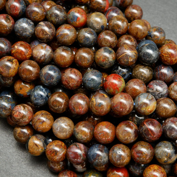 Brown, blue, and red round polished pietersite beads.