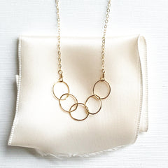 A gold necklace with 5 circles that represents 5 friends