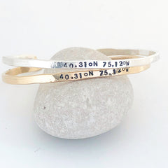 a gold and silver bangle with location coordinates on them