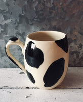 The cowboy mug with cow patterns made of hand-turned porcelain clay