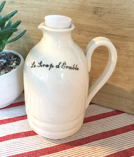 Contenant pour le sirop blanc fait à la main en porcealineWhite Maple syrup pitcher handmade pottery with french or english inscription on white background