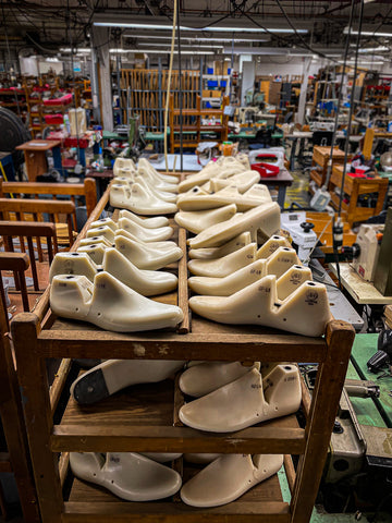 white lasts on a rack in a shoe factory