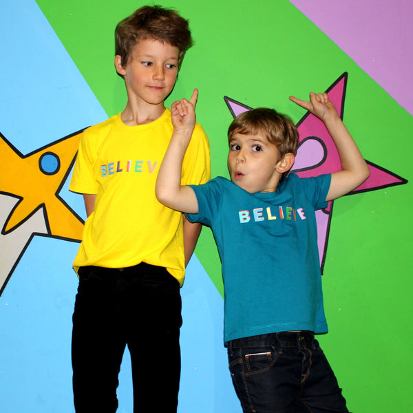 two boys wearing believe tee shirts in teal and yellow