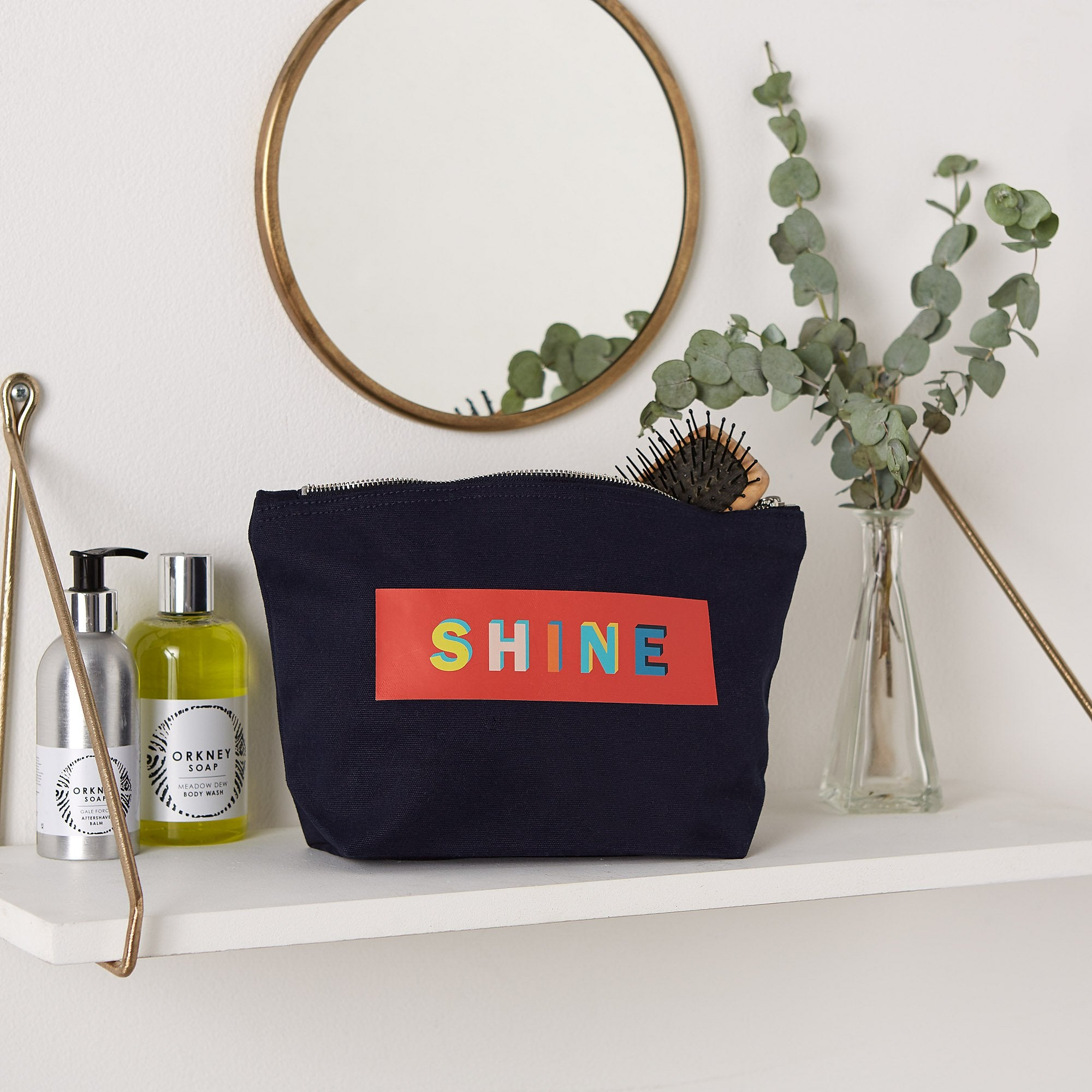 make up pouch with the word shine printed on it in multicoloured print