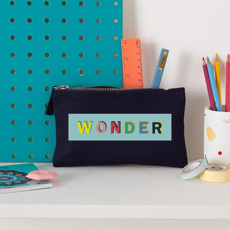 navy pencil case with the word wonder printed on it