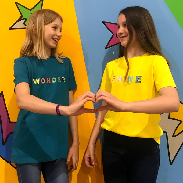 two friends wearing the yellow and teal t shirt colours with the word shine on it