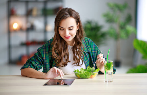 Women eating salad while watching tablet