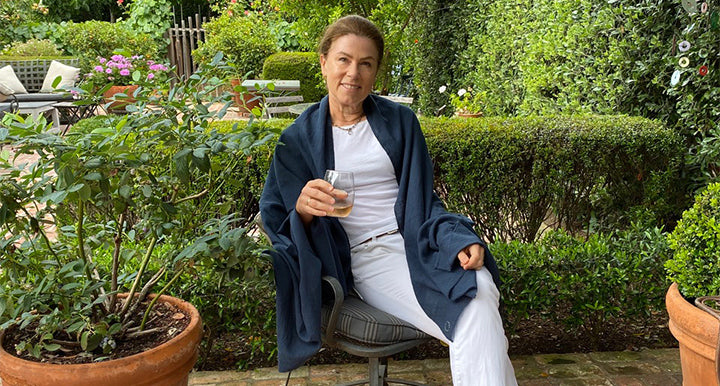 The founder of Shoo for Good, relaxes in her garden with her soft, chic, mosquito-repellent marine (navy blue) wrap draped over her white t-shirt. The 100% cotton shawl is treated with safe, odorless permethrin, so mosquitoes won't bite.
