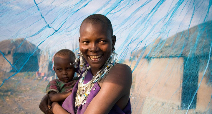 A young African mother holds her son in her arms. A sheer, blue bed net, distributed by Shoo for Good's partner, Nothing But Nets is behind them. She'll sleep well knowing mosquitoes won't bite her son and transmit malaria.