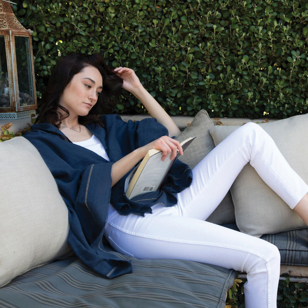 The mosquito-repellent Camellia wrap in marine blue, a navy, is lightweight, super soft, and keeps mosquitoes away. Permethrin is bound to the cotton fibers. The insect-repellency lasts for 70 washings, deterring insects for seasons. The lady wearing the wrap is relaxed in the garden, knowing bugs won't bother her. Insect Shield technology keeps bugs away.