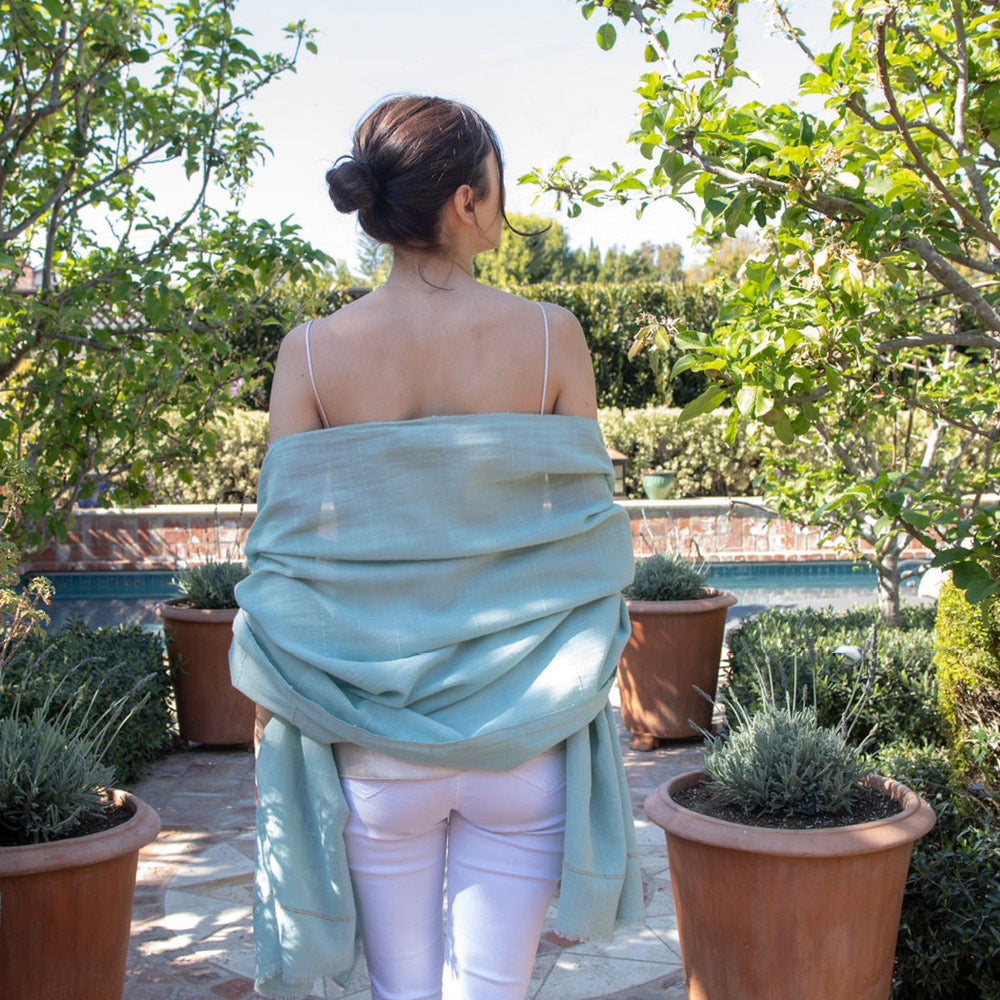 The mosquito-repellent Camellia wrap in sea foam or mint green is lightweight, super soft, and keeps mosquitoes away. Permethrin is bound to the cotton fibers. The insect-repellency lasts for 70 washings, deterring insects for seasons. The lady wearing the wrap is relaxed in the garden, knowing bugs won't bother her. An Oprah favorite!