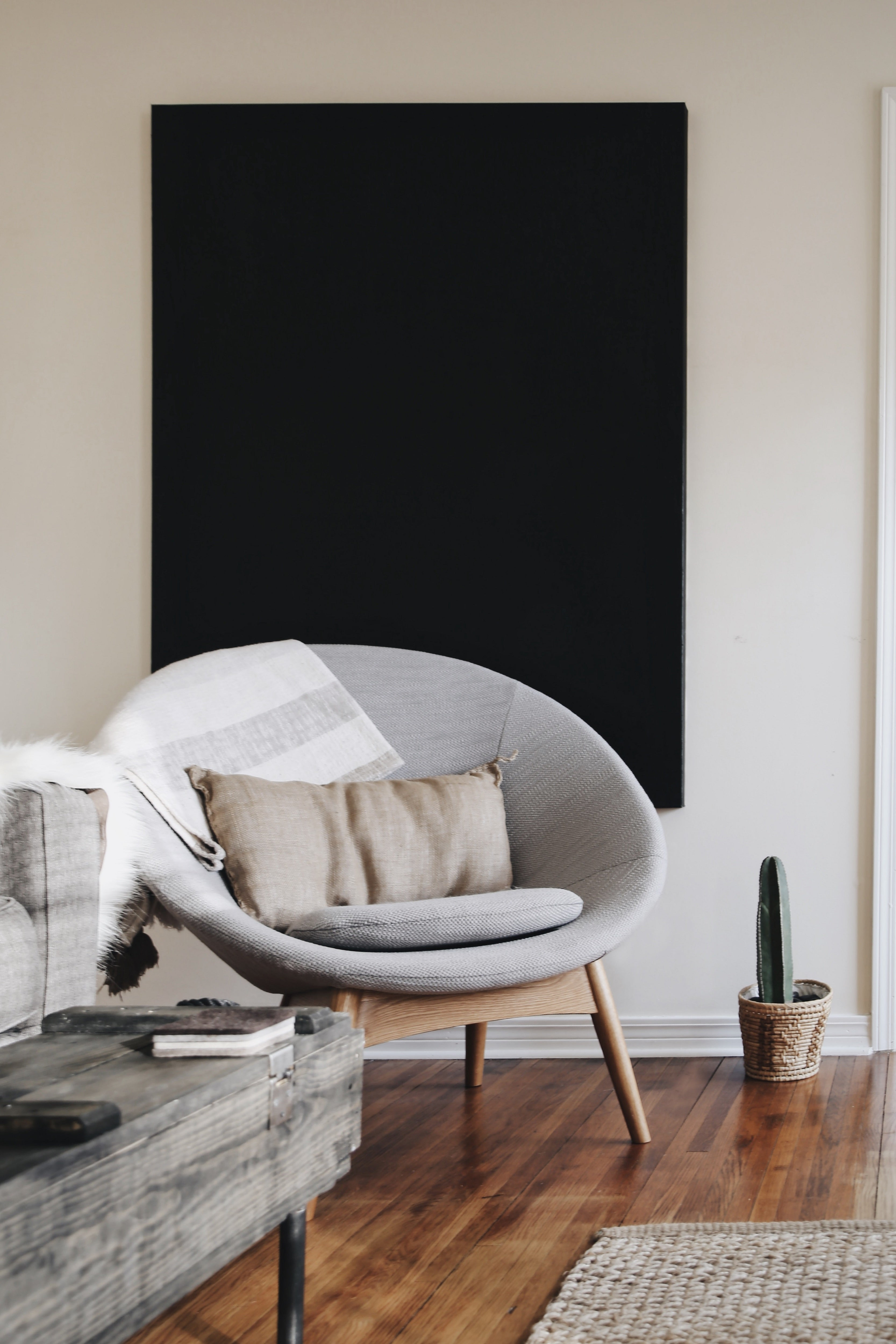 statement artwork, black canvas, heavy black paint, large print on wall behind designer chair, dark wooden floorboards, homely furnishings
