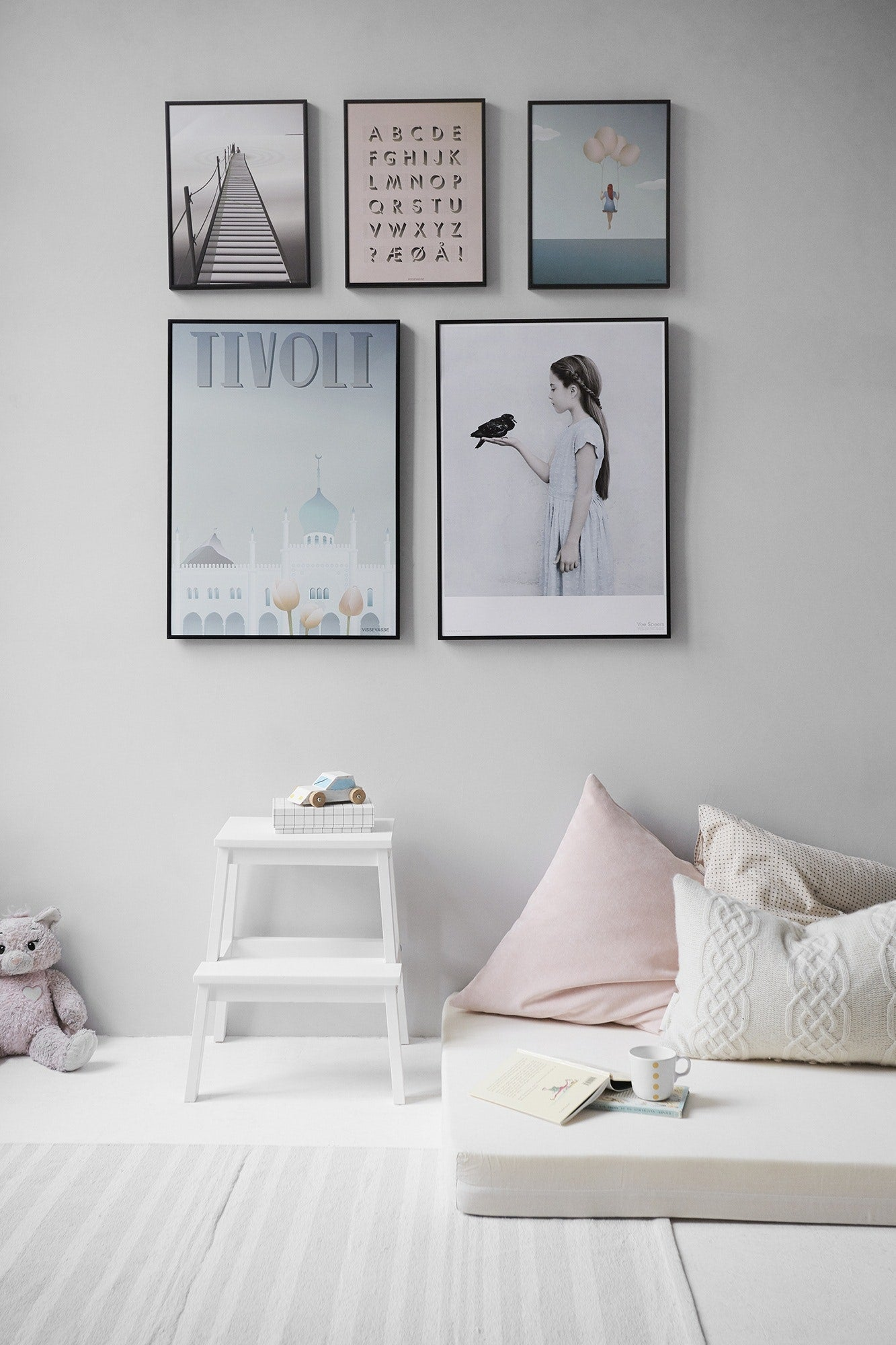 Gallery wall, 3 small frames, 2 large frames, white floorboards, comfortable boho chic living with cushions. White wash floorboards
