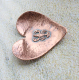 A small 2 inch heart shaped copper ring or trinket dish. There is a raised detailed impression of a lobster in the middle and hammered texture around the edge. The bottom is flat and the three points of the heart are gently curved up. The bowl is oxidized to enhance the details of the lobster and the hammer marks.