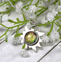 Edelweiss Flower Glass Stone Galaxy PendantEdelweiss Flower Glass Stone Galaxy Pendant. This a one inch wide pendant made in sterling silver. The center is dichroic glass with sparkling bits in a golden color. The silver is shoped like an edelweiss flower. The sterling silver pendant comes on a rolo chain.