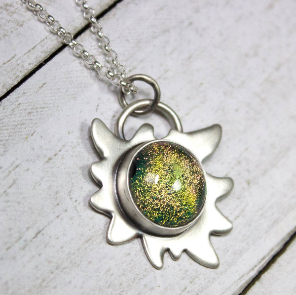 Edelweiss Flower Glass Stone Galaxy Pendant. This a one inch wide pendant made in sterling silver. The center is dichroic glass with sparkling bits in a golden color. The silver is shoped like an edelweiss flower. The sterling silver pendant comes on a rolo chain.