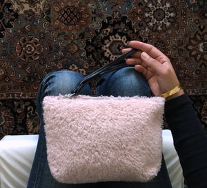 palest pink shearling pouch dressed with denim.