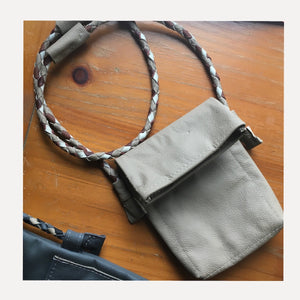 taupe bag with muti color braided strap.