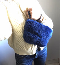 Load image into Gallery viewer, cobalt blue shearling pouch with black leather wristlet.