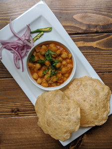 Indian Chole / Chana Bhatura ( Chickpea Curry ) with Bhatura ( puffed flat bread ) on a plate with pickled onions and green chilies