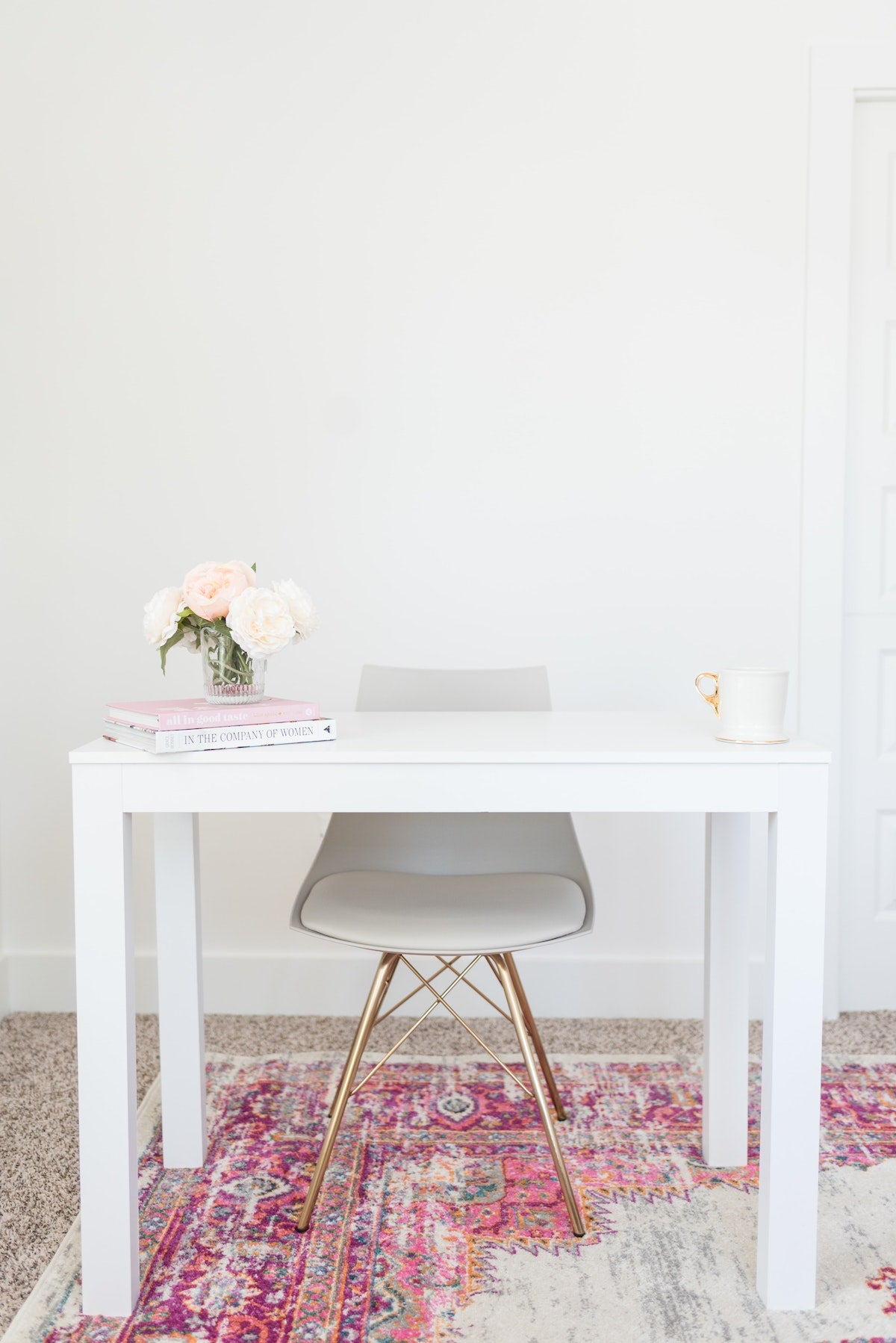 beautifully arranged desk with books and rug