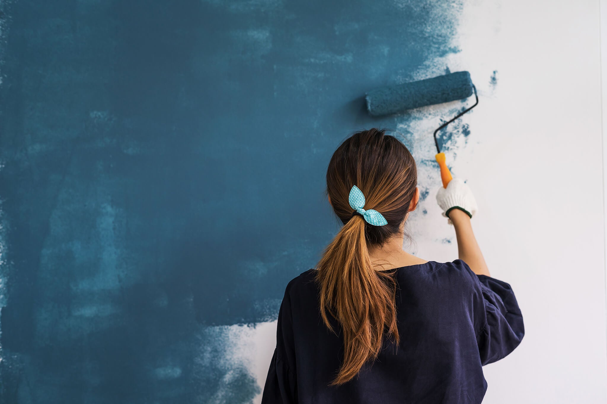 homeowner painting a wall as a cost-effective method of changing a room's design